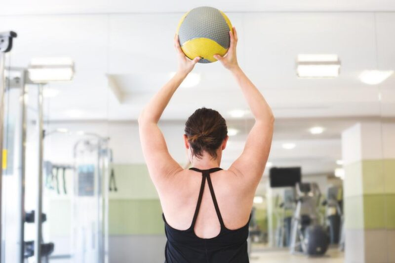 Woman lifting fitness ball